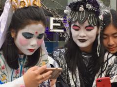 Jeunes filles en costume du jour de l'an chinois avec téléphone portable