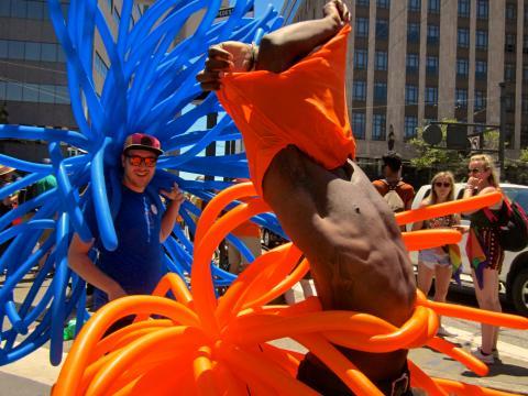 Photo : 2 jeune hommes avec ballons bleus et oranges à la Gay Pride